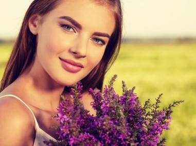 Calm and relaxed beautiful woman  outdoor with flowers in hands.